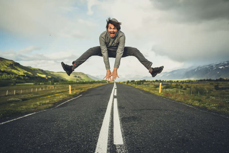 man jumping for joy on road