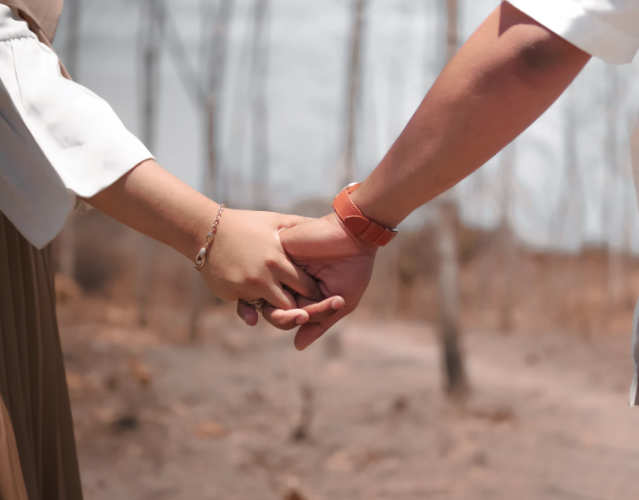 couple holding hands while on a walk